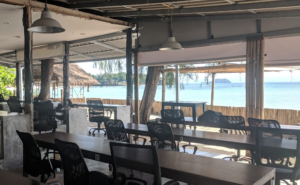 Coworking space directly at the sea. No windows just tables with chairs pointing at blue water and islands